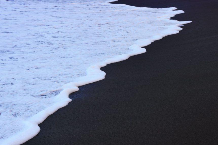 Морской прибой на чёрном пляже