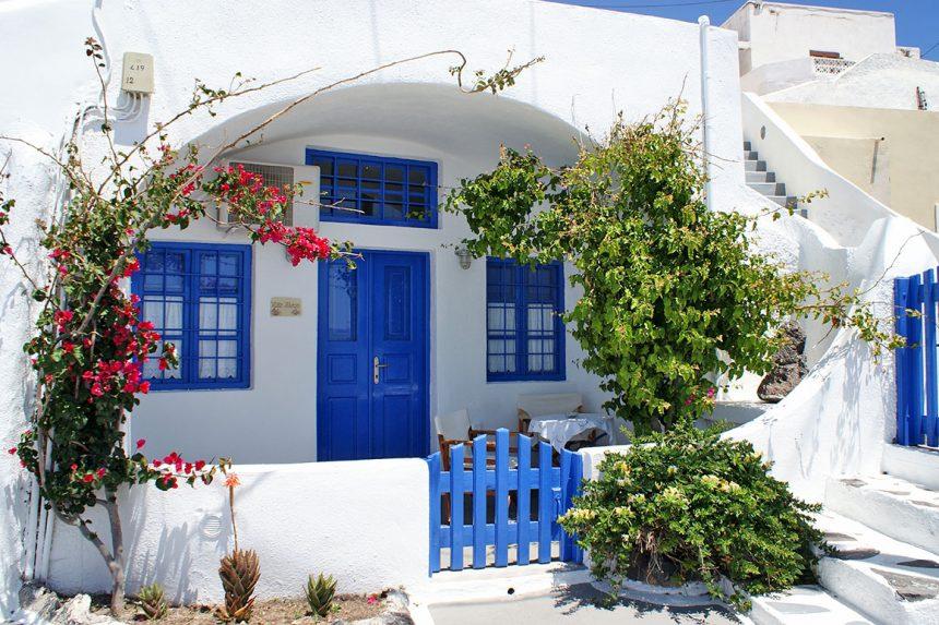 Традиционные белоснежные домики с синими дверями и ставнями в деревне Ия, Санторини